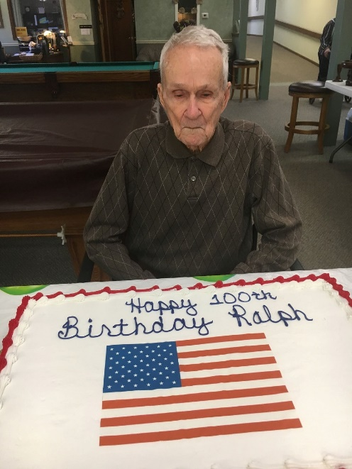 Photo of Ralph, a veteran and resident at Pleasant View Home, and a birthday cake with the American flag celebrating his 100th birthday at the nursing home.